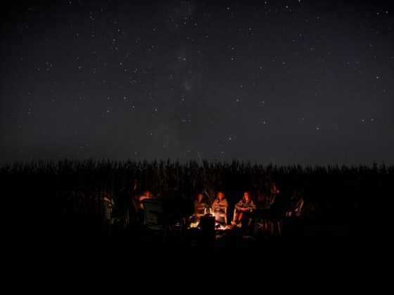 men and women gathering around a campfire