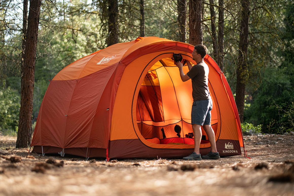 man starting to pack up his orange dome tent